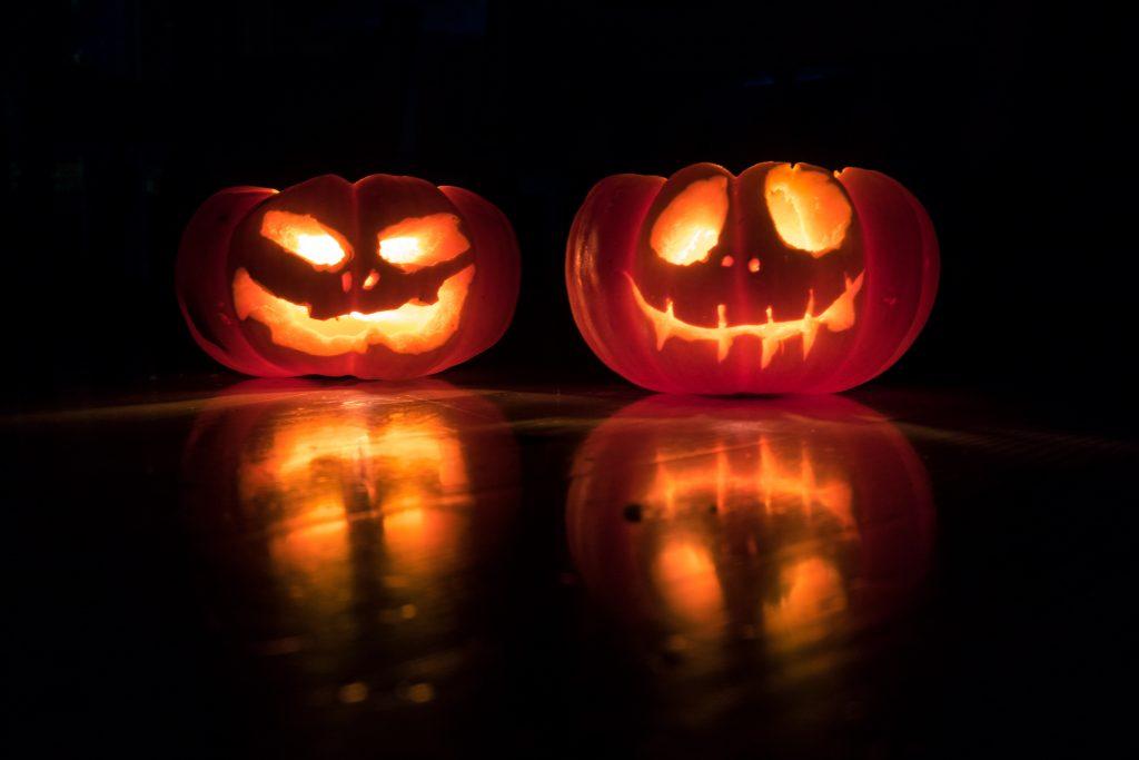 lit pumpkins sit in the dark