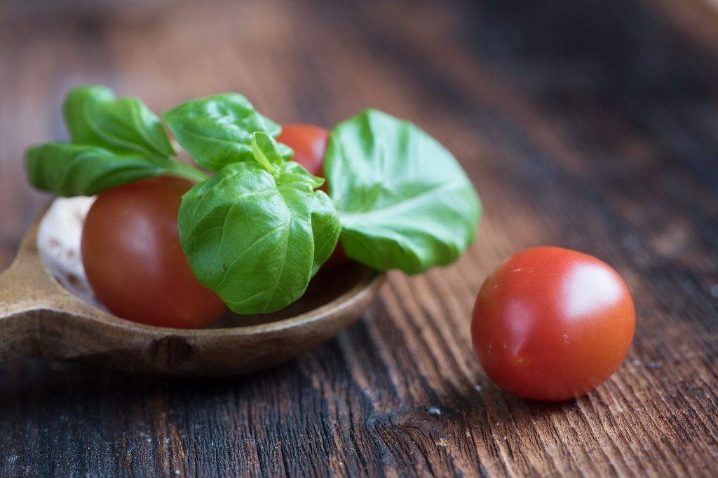 fresh basil and tomatoes sit on a cutting board