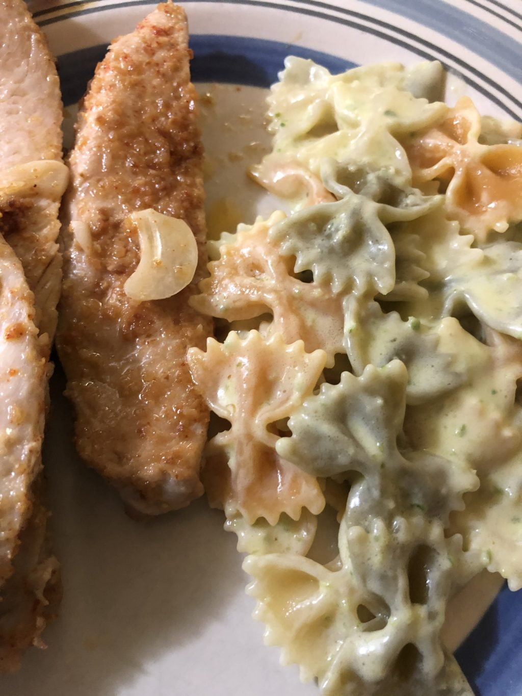creamy pesto pasta on a dinner plate alongside grilled chicken