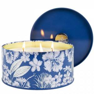 scented candle sitting in a blue container with white flowers