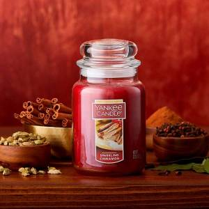 a cinnamon scented candle sits on a cupboard